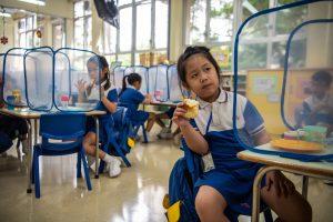 11 Los niños de jardín de infantes comen sus bocadillos detrás de divisores de plástico