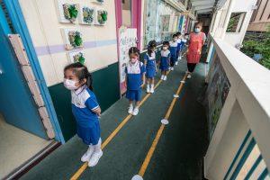 12 Los niños se alinean a lo largo de puntos socialmente distanciados en el suelo para ir al baño