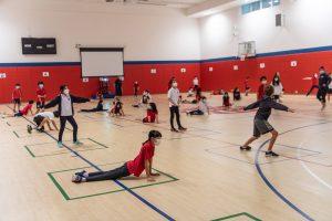 8 Los estudiantes hacen poses mientras mantienen una distancia social durante una clase de educación física